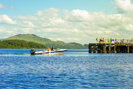 loch lomond: Speed boat with tourists on Summer at Loch Lomond, Luss, Scotland, UK