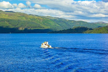 loch lomond: People on the motor boat at the Loch Lomond lake in Scotland
