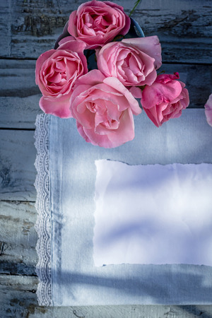 natural love: Beautiful, pink roses on wooden, rustic background with white paper and copy space Stock Photo
