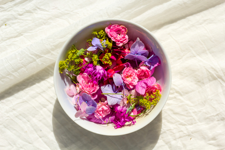 Summer, floral, artistic background with variety of petals and colors in a bowl on cream fabric Stock Photo