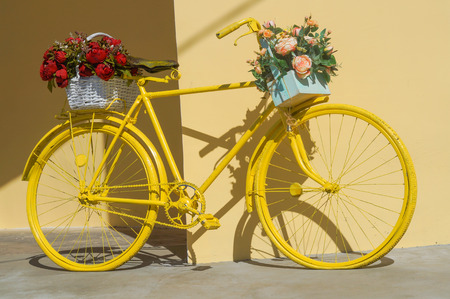 Colorful painted yellow bicycle decorated with flowers