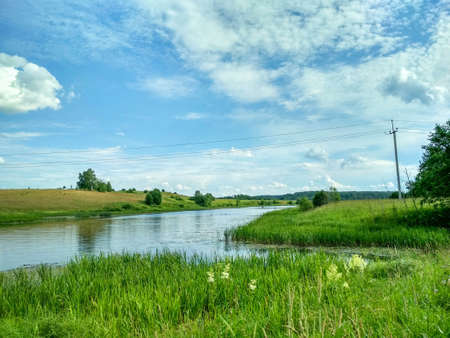 Green summer meadow and river with blue cloudy sky