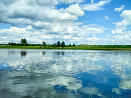 Summer landscape with beautiful white clouds and bright blue sky reflected in the river Stock Photo