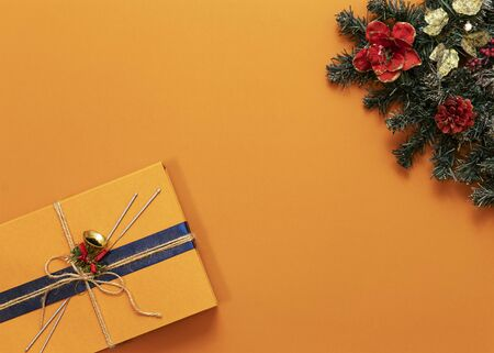 bright orange background, green tree in the upper right corner, orange gift box in the lower left corner, top view, horizontal frame, copy space in the center Stock Photo