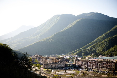 a small town located in high mountains covered with green forest Stock Photo