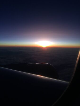 Beautiful sunset or sunrise sky above clouds with dramatic light. Cabin view from airplane Фото со стока