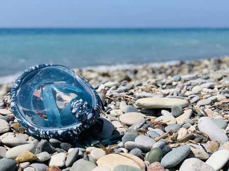 Snorkel gear by the sea. swimming mask scuby on the pebble beach