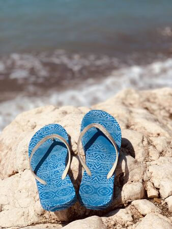 Stylish flip flops on the stone near sea, space for text. Beach accessories