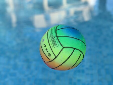 Beach volleyball ball floating in swimming pool. Copy space