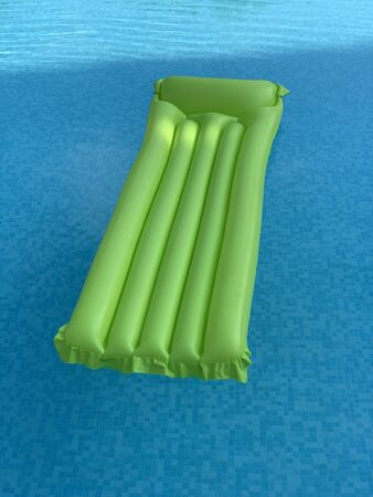 green inflatable mattress floating on water surface