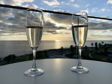 two glasses of champagne at hotel balcony with view of sea and skyline, luxury romantic dinner for couple. romantic holiday Reklamní fotografie