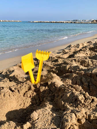 Bright plastic children's toys in the sand. Concept of beach recreation for children. Top view. shovel and rake