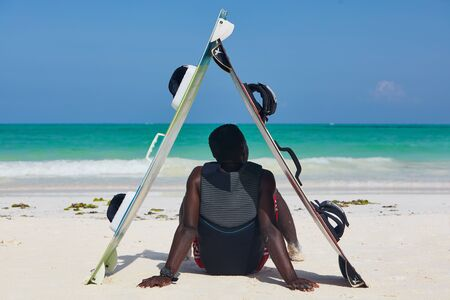 A man relaxing in shade kiteboards sitting down facing the ocean, wave and sky