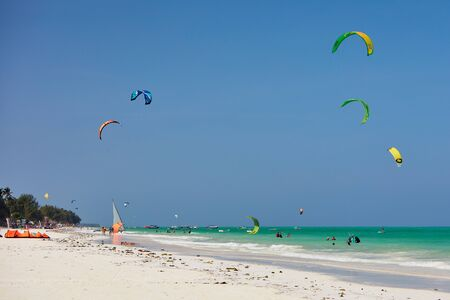 People with kites in the sky at spot at the ocean beach with trees and palmtrees Stock Photo
