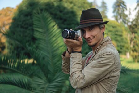Authentic gray-haired beautiful man in a green hat with a camera on a background of palm trees in the park.