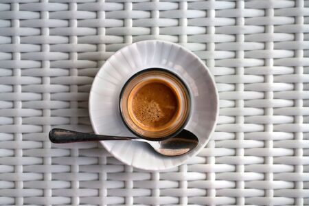 Hot aromatic espresso with froth. A freshly prepared drink served in a modern cup on a light wicker table. Stockfoto