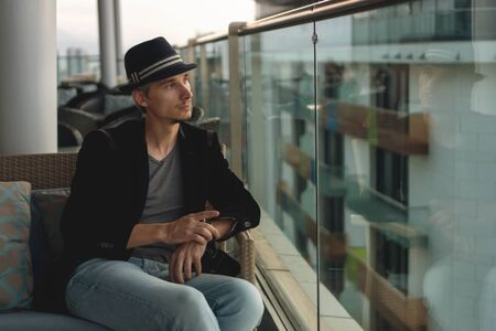 Pensive man in a hat sits on a hotel terrace and looks at a neighboring building.  He took up his watch and thinks of something. Reklamní fotografie