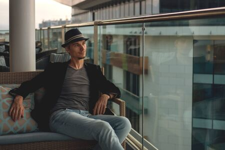 Authentic man relaxed on a sofa on a hotel balcony.