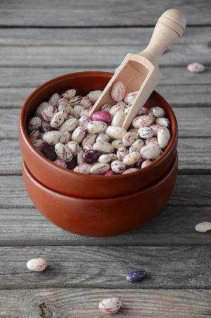 borlotti beans: Borlotti beans in a ceramic bowl on the rustic wooden table Stock Photo