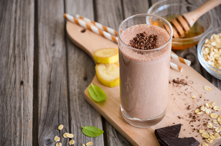 Chocolate and banana smoothie with oatmeal on the rustic wooden table