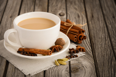 Indian masala chai tea. Spiced tea with milk on the rustic wooden table. Horizontal permission. Selective focus.