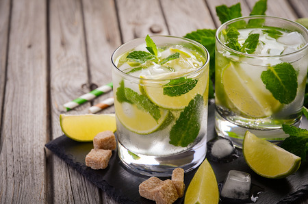 Fresh mojito cocktail with lime and mint on rustic wooden background