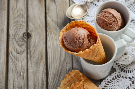 epicure: Chocolate ice cream in waffle cone on rustic wooden background