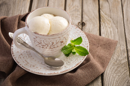 epicure: Vanilla ice cream in cup on rustic wooden background