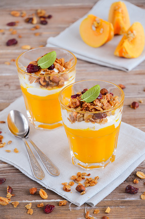 Pumpkin pudding with granola and yogurt on rustic wooden table