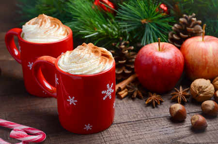 apple cinnamon: Hot chocolate with whipped cream in red cups. Christmas composition.