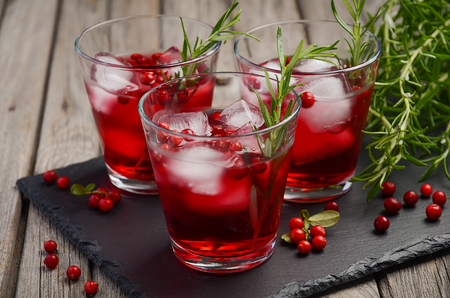 mountain cranberry: Refreshing drink with cranberries and rosemary on wooden background