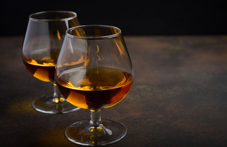 Glass of brandy or cognac on the old rusty background