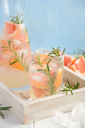 Summer refreshing drink with grapefruit and rosemary, selective focus, copy space