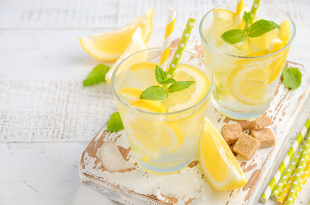Cold refreshing summer drink with lemon and mint on wooden background. Stock Photo