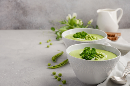 Green pea soup in bowls on a gray background, selective focus, copy space