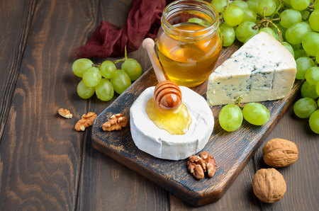 Variety of cheese with grapes, walnuts and honey. Stock Photo
