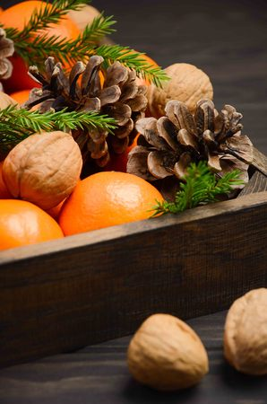 Fresh tangerine clementine with nuts and cones in a wooden tray on a dark wooden background.