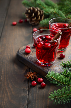 Cranberry drink on a wooden background decorated with fir branches, spices and fresh berries, selective focus.