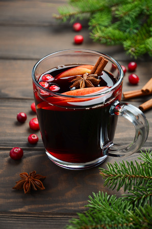 Christmas Mulled Wine with Apple and Cranberries. Holiday Concept Decorated with Fir Branches, Cranberries and Spices. Stock Photo