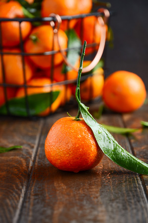 Fresh tangerine clementines with leaves on a dark wooden background, selective focus. Stock Photo