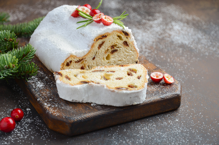 Christmas Stollen. Traditional German, European Festive Dessert. Holiday Concept Decorated with Fir Branches and Cranberries.