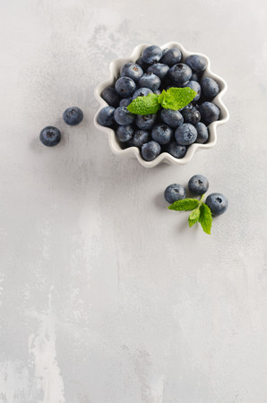 Ripe sweet blueberries in white bowl on a gray background, top view, flat lay, copy space.