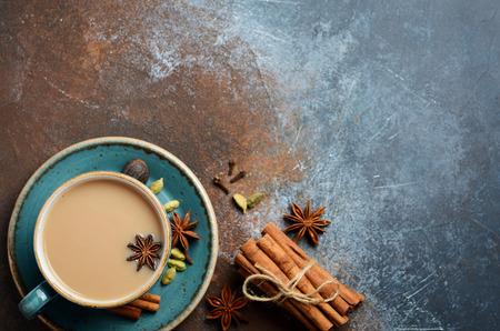 Indian masala chai tea. Spicy tea with milk on dark rusty background.