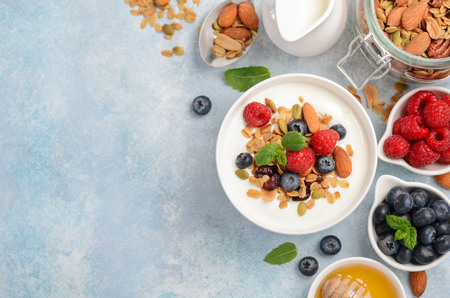 Homemade granola with yogurt and fresh berries, healthy breakfast concept, top view, copy space. Stok Fotoğraf