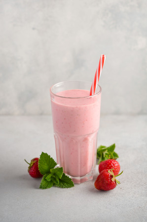 Strawberry milkshake on a gray concrete background, selective focus.