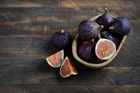 Fresh figs in a wooden bowl on an old wooden background.