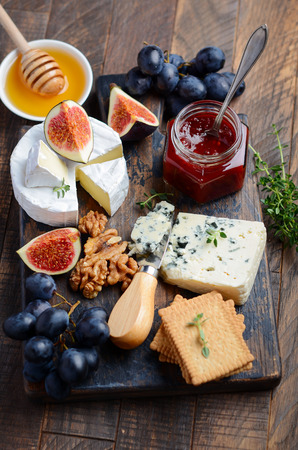 Cheese plate with grapes, figs, crackers, honey, plum jelly, thyme and nuts, selective focus.