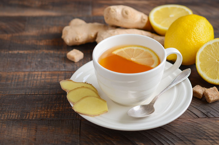 Ginger root tea with lemon and honey on a wooden background. Stock fotó