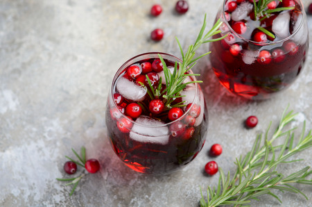 Cold refreshing drink with cranberry and rosemary