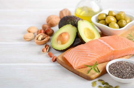 Selection of healthy unsaturated fats, omega 3 - fish, avocado, olives, nuts and seeds.